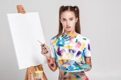 Woman painter soiled in colorful paint draws on canvas. Stock Photos
