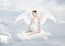 Beautiful young woman as angel sitting on a cloud. With white heart and halo royalty free stock image