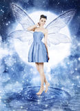 Beautiful young woman as blue fairy. Night glamour portrait with moon royalty free stock image