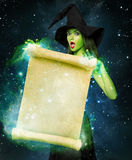 Beautiful young woman as halloween witch. With scroll-magical portrait Royalty Free Stock Photos
