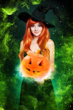 Beautiful young woman as halloween witch. With scroll-magical portrait Stock Photos