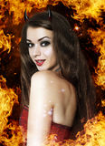Beautiful young woman as devil. Beautiful young brunette woman as devil in fire royalty free stock photo