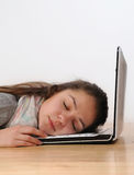 Beautiful young woman asleep on her laptop against a white backg Royalty Free Stock Photography