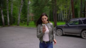 Young woman is talking on the phone on the run, she is in a hurry. outdoors in summer. slow-motion stock video