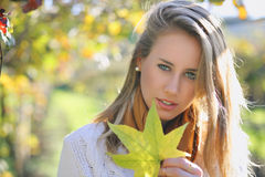 Beautiful young woman with autumn leaf Stock Images