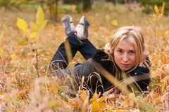 Beautiful young woman in autumn leaves Royalty Free Stock Photography