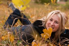 Beautiful young woman in autumn leaves Stock Photo