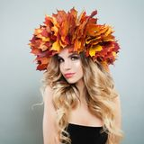 Beautiful young woman in autumn leaves crown portrait. Pretty model with makeup and curly hair.  royalty free stock photo