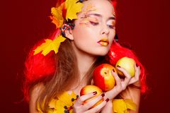 Beautiful young woman with autumn make up holding apples in her royalty free stock photography