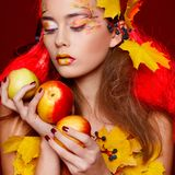 Beautiful young woman with autumn make up holding apples in her stock images