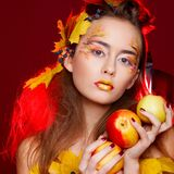 Beautiful young woman with autumn make up holding apples in her royalty free stock photo