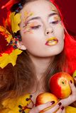 Beautiful young woman with autumn make up holding apples in her stock photography