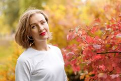 Beautiful young woman in autumn park. Season and people concept. Blonde fashion model having fun in fall park outdoors. Stock Images