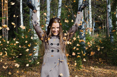 The beautiful young woman in autumn wood. The beautiful young woman has fun throwing upwards autumn leaves stock photography