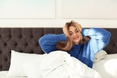 Beautiful young woman awaking in bed at home. Winter atmosphere stock image