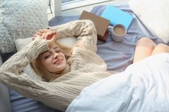 Beautiful young woman awaking and smiling at home, top view. Winter atmosphere stock images