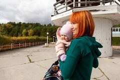 Beautiful young woman with baby. Atmospheric lifestyle photo of young beautiful redhaired women in a green jacket walks and plays with his little daughter baby royalty free stock image