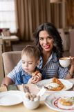 Beautiful young woman with baby son. Light breakfast near window in a cafe. Croissants, omelet, coffee and many. Beautiful young women with baby son. Light royalty free stock image