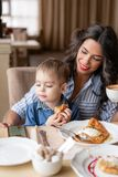 Beautiful young woman with baby son. Light breakfast near window in a cafe. Croissants, omelet, coffee and many. Beautiful young women with baby son. Light stock photo
