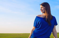Beautiful young woman on the background of sky and field Stock Photo