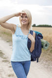 Beautiful young woman with backpack shielding eyes while hiking at field Stock Image