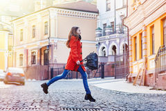 Beautiful young woman with bag in orange coat walking on the street Stock Image