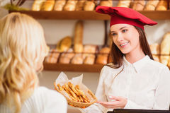 Beautiful young woman at bakers shop stock images