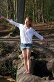 Beautiful young woman balancing on a log across a stream Stock Image