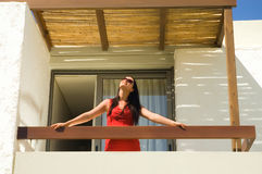 Beautiful young woman on the balcony. On sunny day stock photo