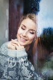 Beautiful young woman on a balcony behind the glass Royalty Free Stock Photos