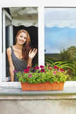 Beautiful young woman on a balcony greeting someone Royalty Free Stock Image