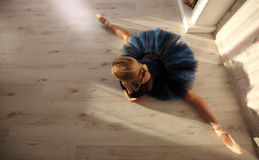 Beautiful Young Woman Ballerina Stretching Warming Up In home Interior, split on wooden floor. Beautiful Young Woman Ballerina Stretching Warming Up Royalty Free Stock Photos