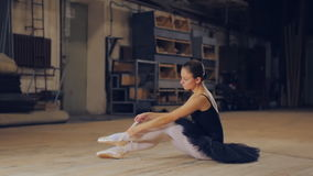 Beautiful Young Woman Ballerina Tying Pointe Shoes On The Background Of Wooden Wall. Ballerina tying pointe ballet shoes on stage stock video