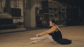 Beautiful Young Woman Ballerina Tying Pointe Shoes On The Background Of Wooden Wall. Ballerina tying pointe ballet shoes on stage stock footage