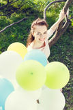 Beautiful young woman with balloons sitting on tree Stock Photography