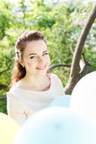 Beautiful young woman with balloons sitting on tree Royalty Free Stock Images