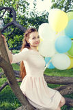Beautiful young woman with balloons sitting on tree Stock Image