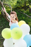 Beautiful young woman with balloons sitting on tree Royalty Free Stock Photos