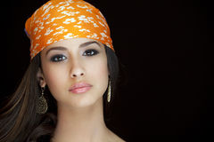 Beautiful Young Woman with Bandanna. Beautiful and exotic young woman of multiple ethnicity wearing a orange bandanna on a black background royalty free stock image