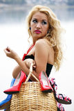 Beautiful young woman with a basket full  of shoes Stock Photography