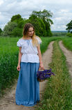 Beautiful young woman with basket of wild flowers. Beautiful young woman stands with basket of wild flowers on rural road among fields Stock Photography