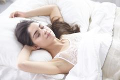 Beautiful young woman basking in bed in the morning. Beautiful Model face looks in camera.  royalty free stock photography