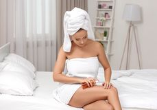 Beautiful young woman after bath applying body oil onto skin. At home Stock Image