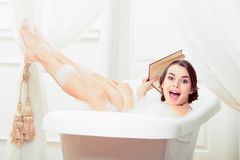 Beautiful young woman in bath with a book Royalty Free Stock Photography