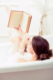 Beautiful young woman in bath with a book Stock Image