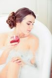 Beautiful young woman in bath with a wine glass Stock Photos