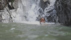 Beautiful young woman relaxing swimming under tropical waterfall. slow motion. 3840x2160. Beautiful young woman bathing relaxing under tropical waterfall. slow stock footage