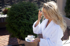 Beautiful young woman in Bathrobe sitting on terrace and drink coffee Royalty Free Stock Photography