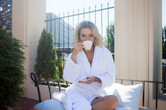 Beautiful young woman in Bathrobe sitting on terrace and drink coffee Royalty Free Stock Photo