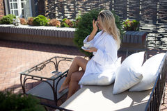 Beautiful young woman in Bathrobe sitting on terrace and drink coffee Royalty Free Stock Image